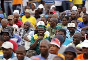 Mine workers listen as they are addressed by their leader outside the Lonmin mine in Rustenburg